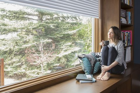 Thoughtful woman drinking coffee at window seat in home office