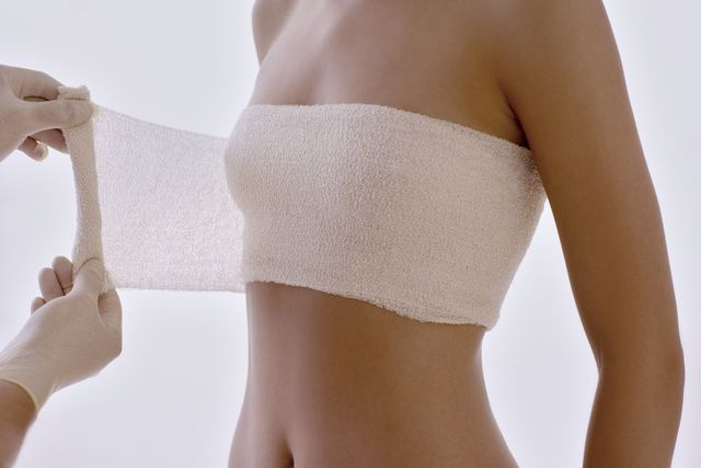 cosmetic breast surgery cosmetic surgeon applying a protective bandage round the clients breasts after surgery