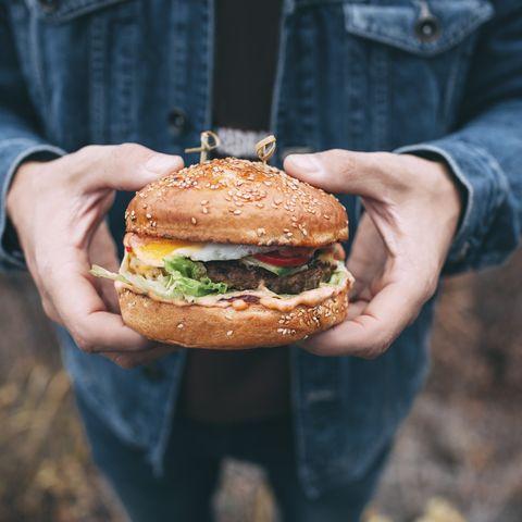 man holding a burger men's health
