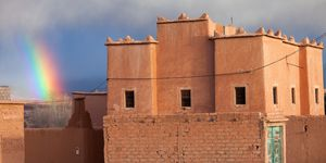 Rainbow over a traditional house in Morocco in desert