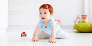 cute infant baby crawling on the floor at home