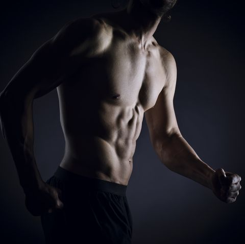 sportlicher muskulöser mann mit definierten muskeln posiert vor schwarzen hintergrund