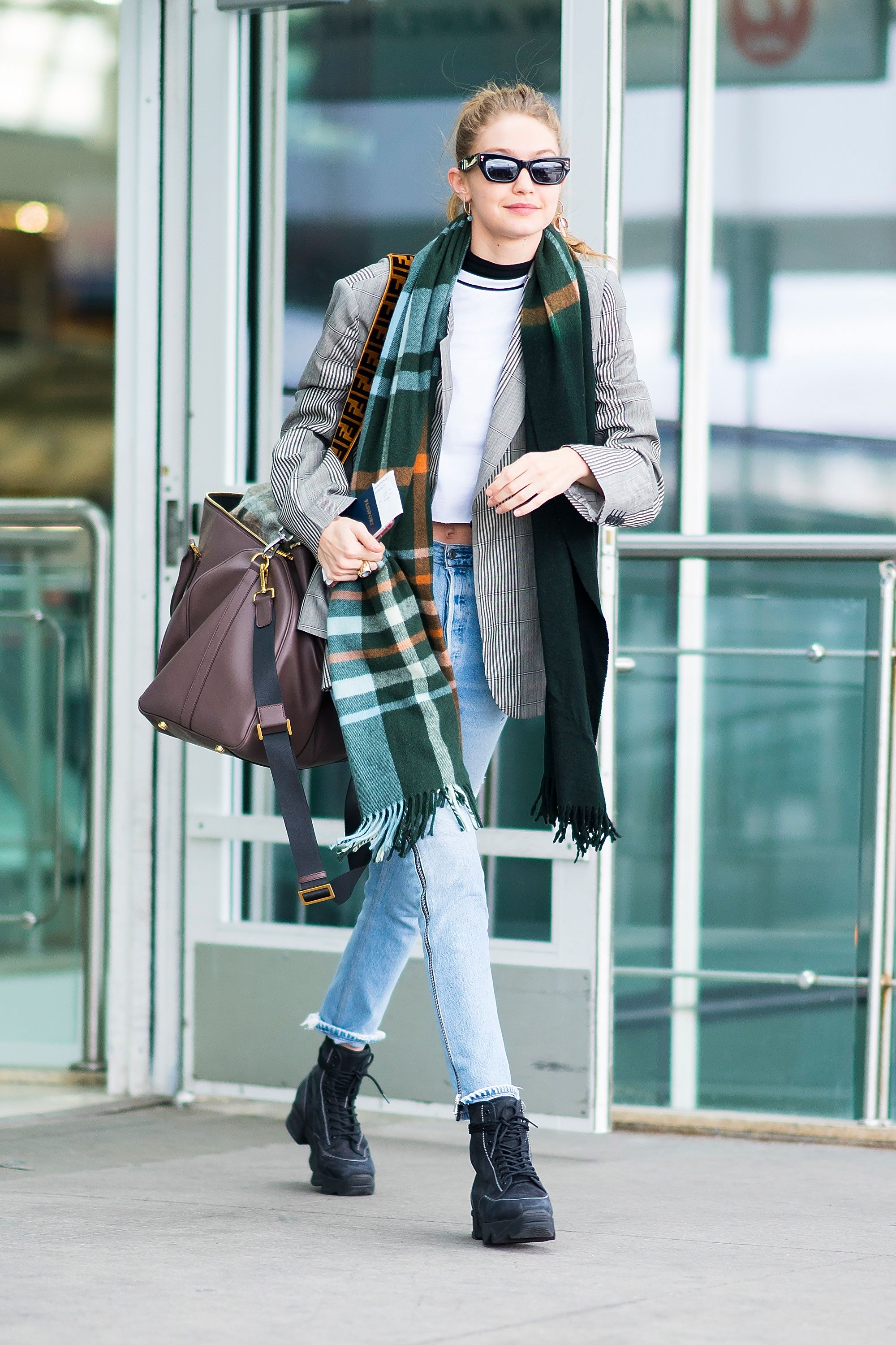 March 4, 2018 Hadid landed at JFK airport in a layered ensemble. She looked warm and comfortable in a Pared x Bec scarf, striped blazer, white crop T-shirt, blue jeans, and black boots.