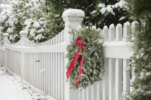 Christmas wreath hanging on white fence covered in snow
