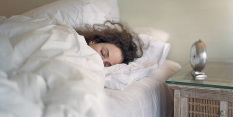 Sleeping woman snuggles in the warmth of a down comforter
