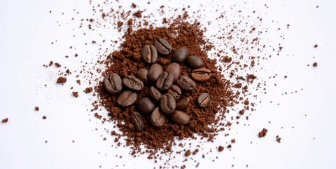 high angle view of ground coffee and beans over white background