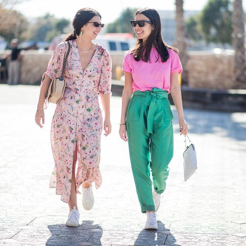 tel aviv, israel   march 13 sisters dana cohen wearing dress with floral print, sneakers and yarden cohen wearing pink shirt, green pants, bag, converse shoes is seen during tel aviv fashion week on march 13, 2018 in tel aviv, israel photo by christian vieriggetty images