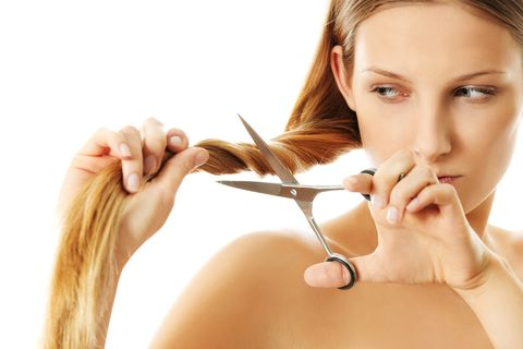 Close-Up Of Woman Cutting Her Hair Against White Background