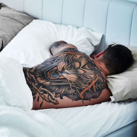 Rear View Of Man With Tattoo Sleeping On Bed