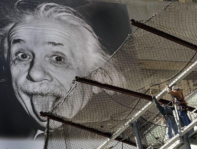 a billboard with a picture of albert einstein hangs in the background as construction workers put up safety netting on a building in times square in new york on april 16, 2009         afp phototimothy a clary photo credit should read timothy a claryafp via getty images
