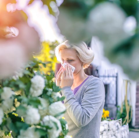 Women blowing her nose next to flowers