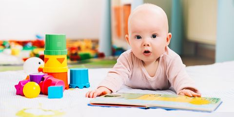 Adorable 6 months old baby looking and reading a book.