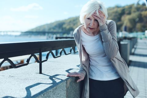 need to take my pills exhausted older lady leaning on a barrier and touching her forehead while suffering from a terrible headache outdoors
