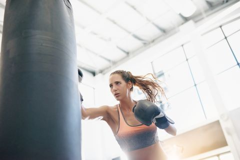 Punching bag, Boxing glove, Arm, Boxing, Physical fitness, Sport venue, Room, Leg, Sports training, Muscle,