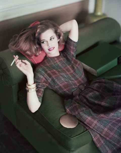 actress jane fonda, lying back on a couch, wearing a plaid dress and smoking a cigarette  photo by horst p horstconde nast via getty images  local caption  jane fonda