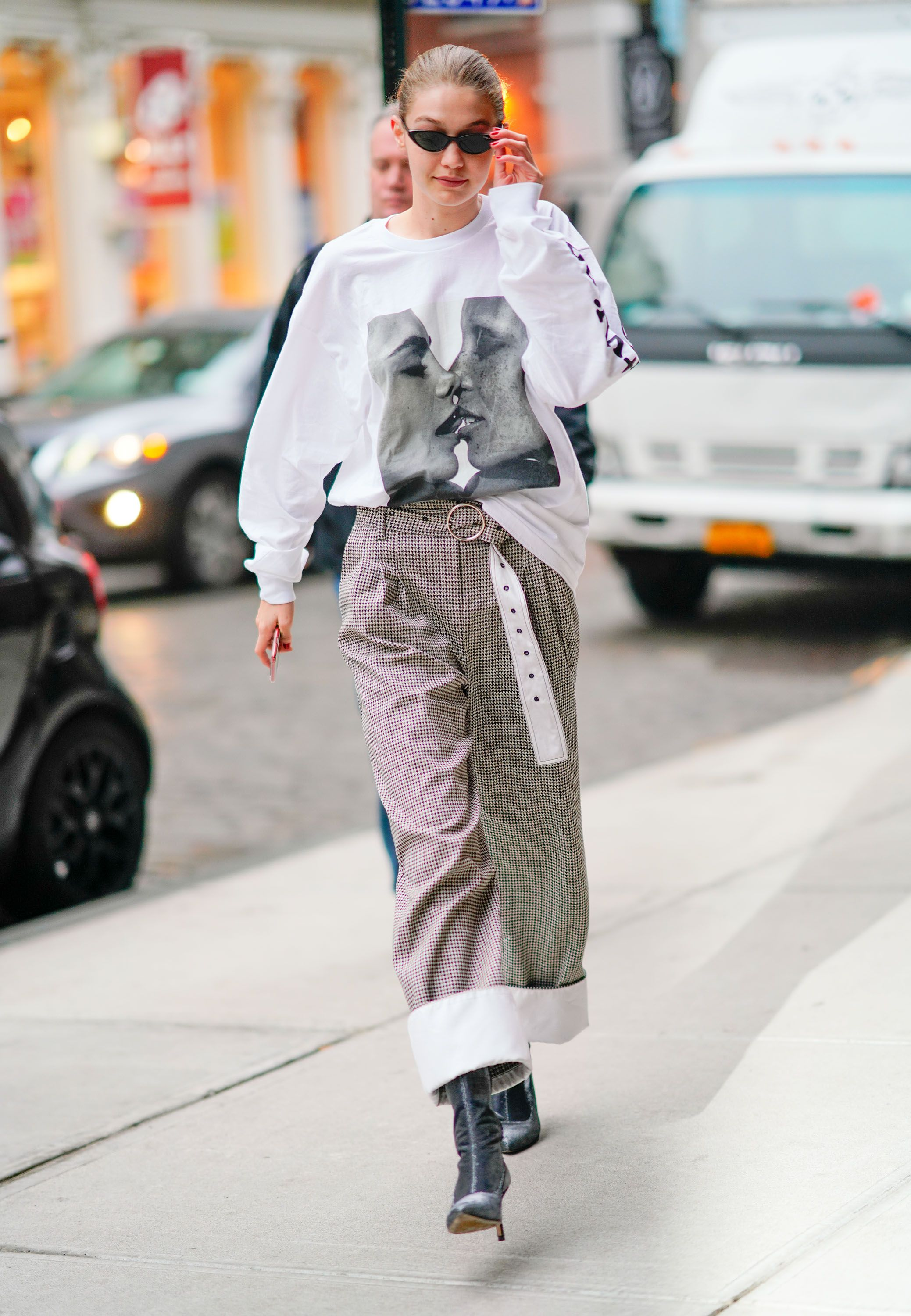 March 29, 2018 Your eyes will zoom right on to Hadid's Chaos SixtyNine shirt , which features Cara Delevingne and Adwoa Aboah going in for a kiss. She tucked the oversize top into high-waisted checkered (dare we say Santa Clause–inspired) pants and wore a pair of Stuart Weitzman boots.