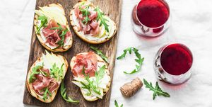 Bruschetta with cream cheese, pear, prosciutto, arugula on wooden chopping board and red wine on light background, top view. Flat lay