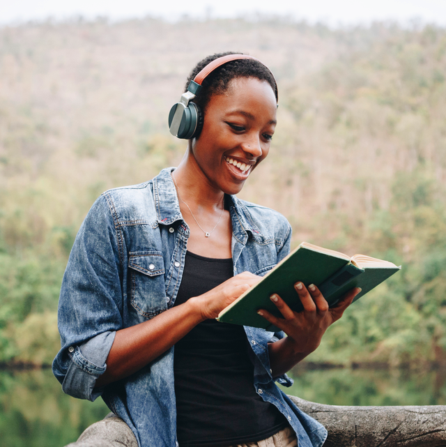 black woman reading book with nature background