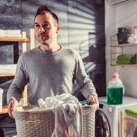 Man wearing gray sweater carrying basket of cleaner clothes at washroom