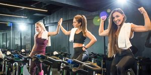Pretty fitness girls celebrating after successful cycling class in gym.