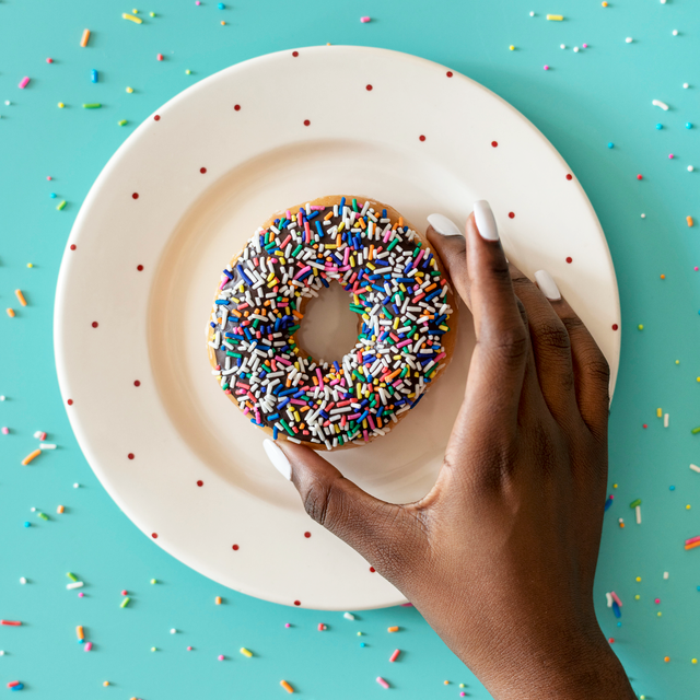 black hand holding donut with sprinkles over plate on blue background