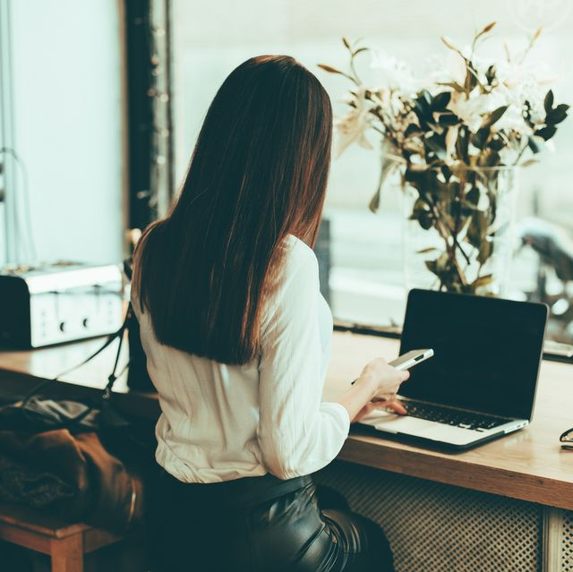 Back view of businesswoman using laptop and cell phone in a coffee shop
