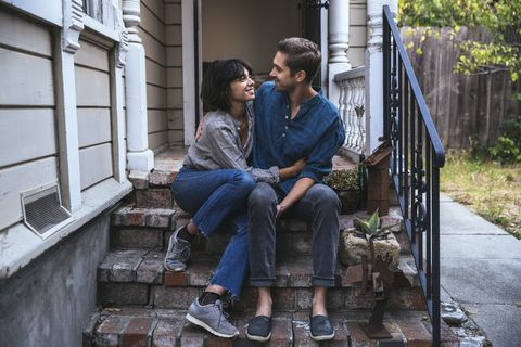 Happy couple sitting on stoop embracing