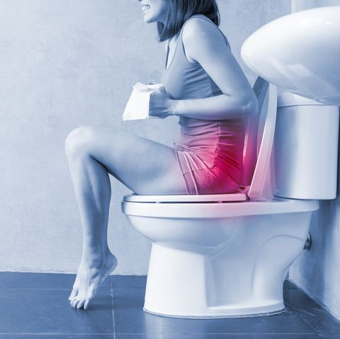 women sat on the toilet suffering from constipation