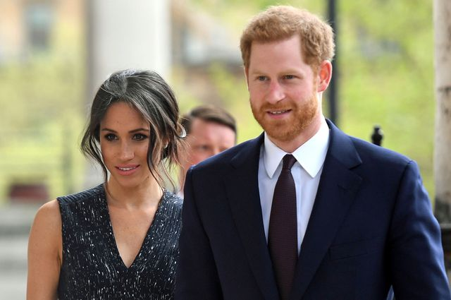 a photo of meghan markle and prince harry walking together outside