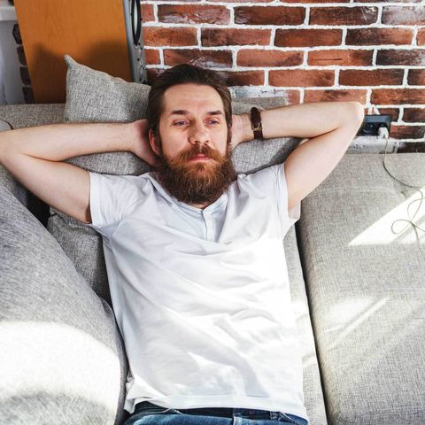 man reclining on sofa with serious expression