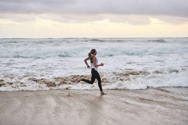 female running barefoot on beach