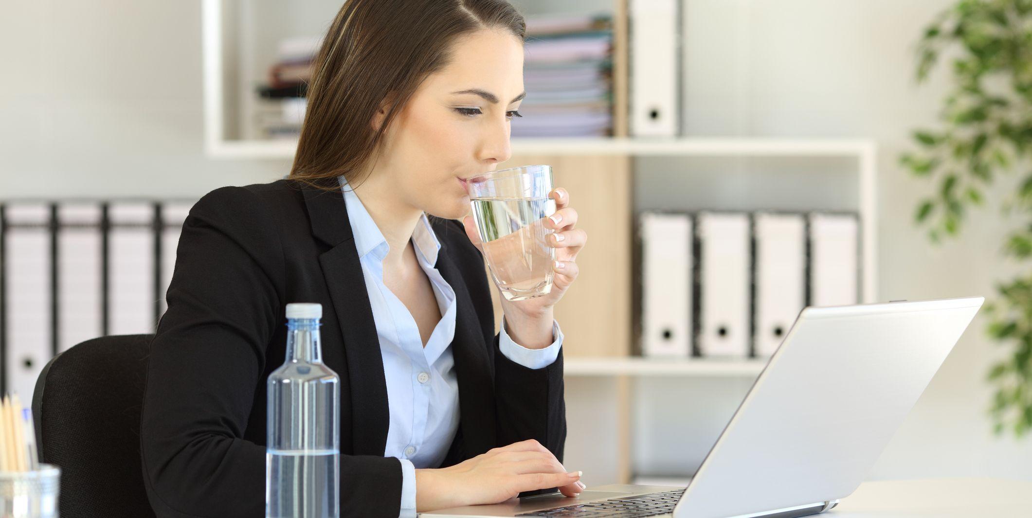 Office worker drinking water working on line