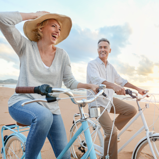 middle age couple riding vintage bicycles on beach at sunset