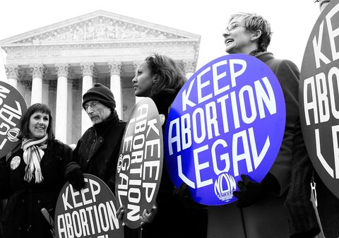 woman holding a sign that says keep abortion legal