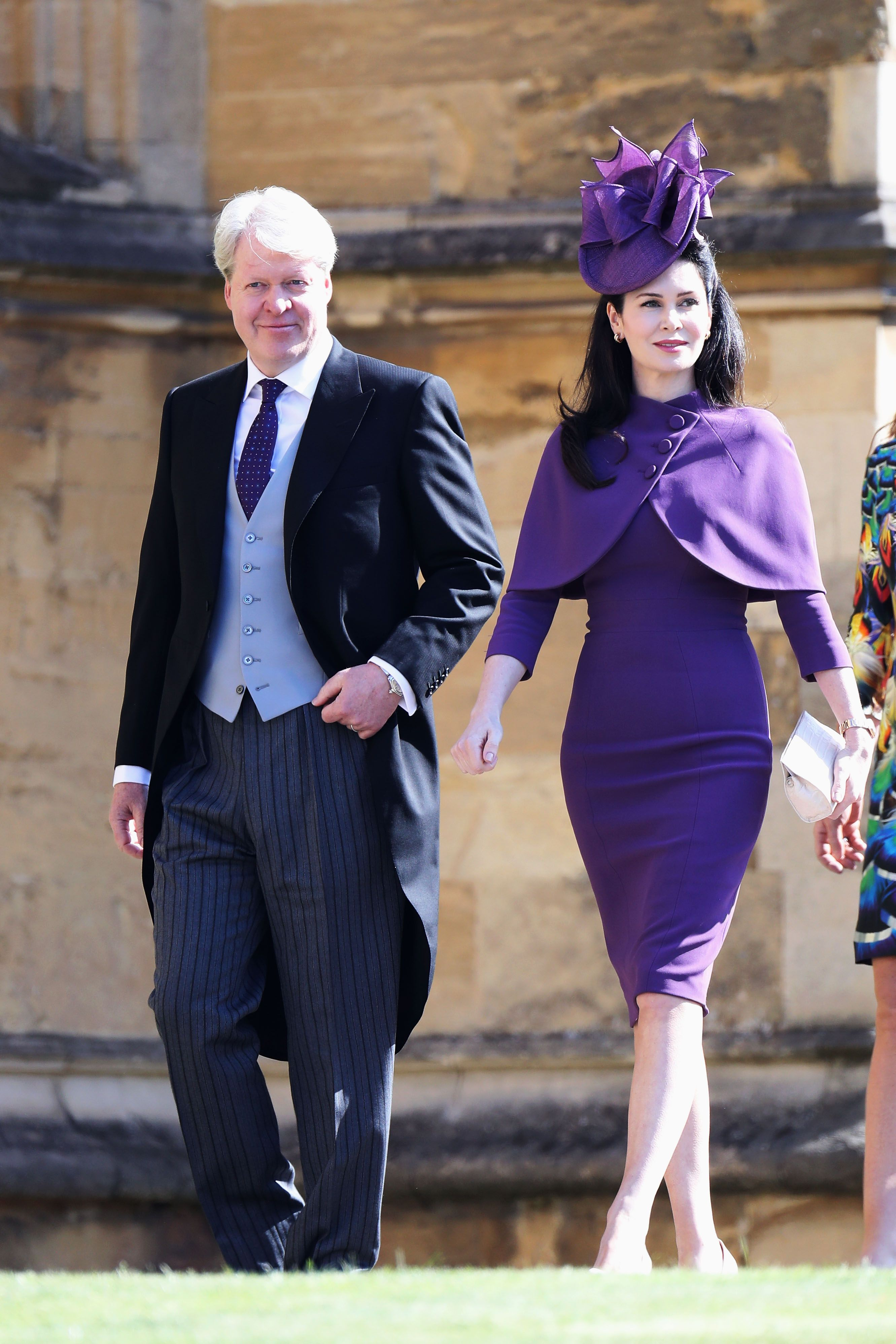 Princess Diana's brother Charles Spencer wears a traditional morning suit. Karen Spencer is dressed in a royal purple capelet and form-fitting knee-length dress.