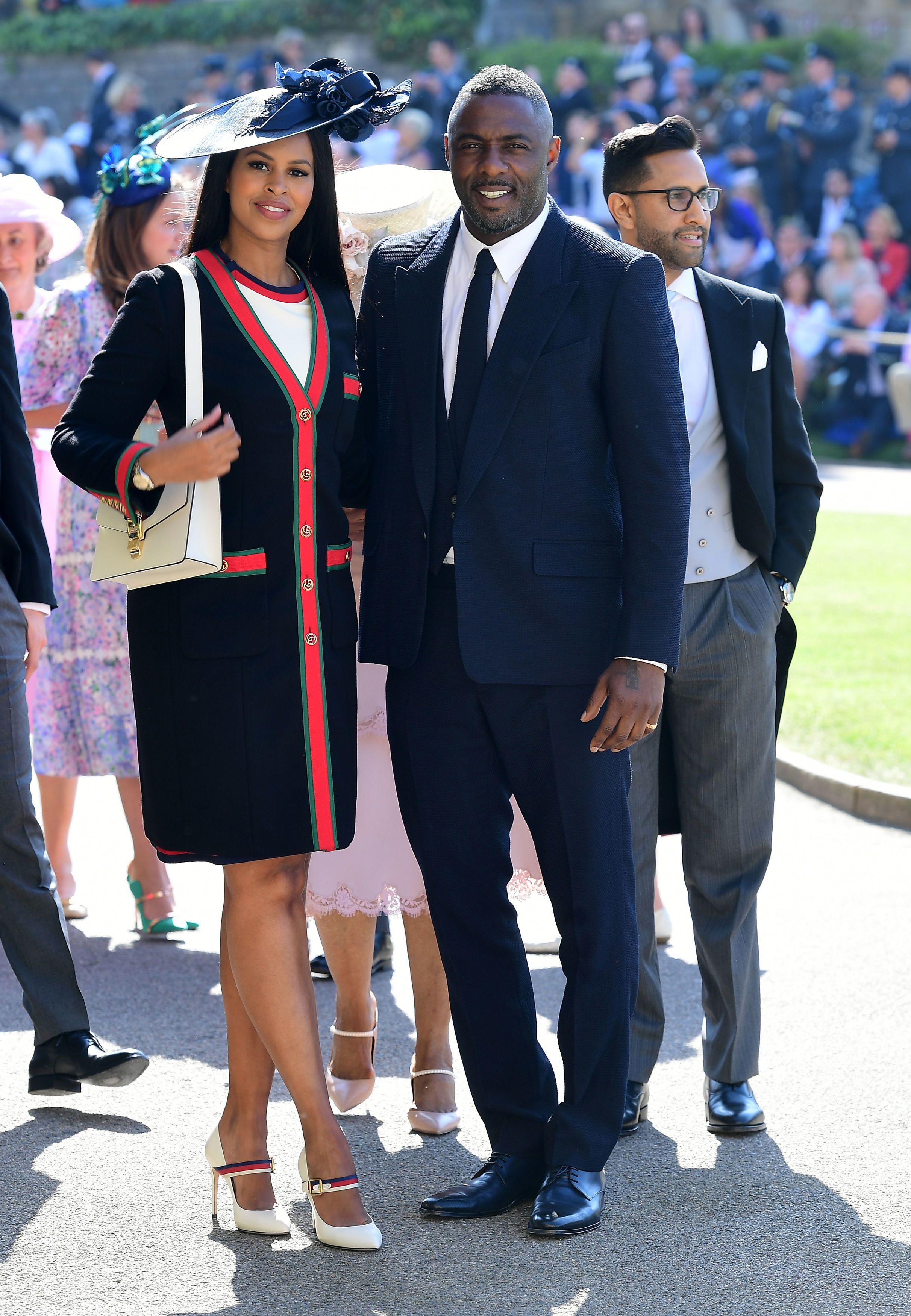 Elba's model fiance is dressed in head-to-toe Gucci; the actor is wearing a navy Givenchy suit.