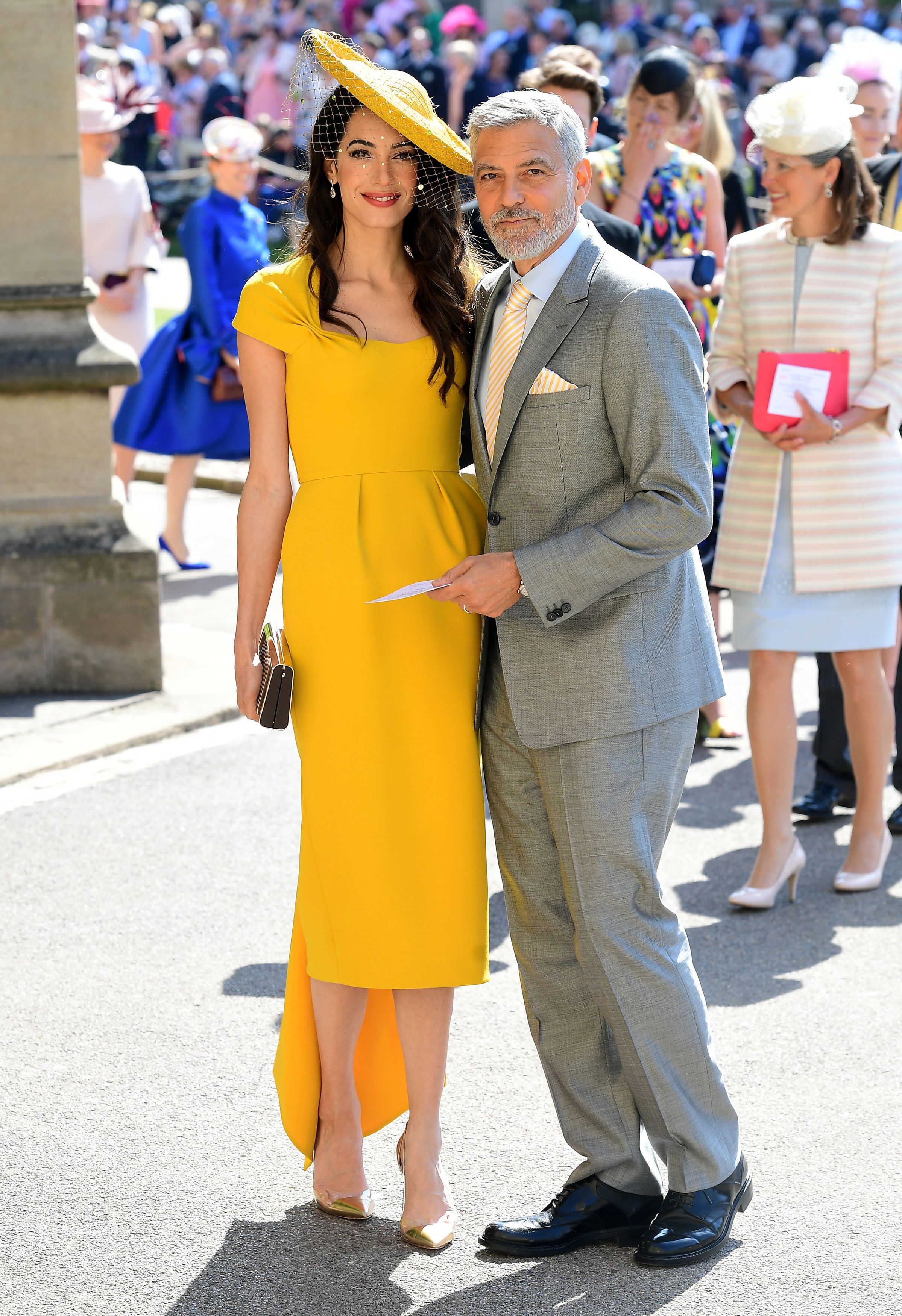 Amal wears a honey yellow midi dress with side drape detail in silk by Stella McCartney with a head dress by Stephen Jones. George is dressed in a light gray lounge suit with a striped tie and pocket square.