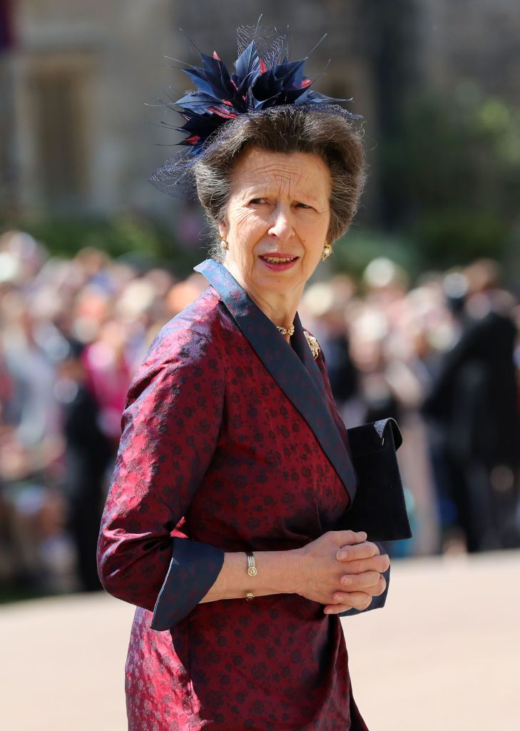 Princess Anne wears a deep red dress with navy lapels and a navy floral fascinator.