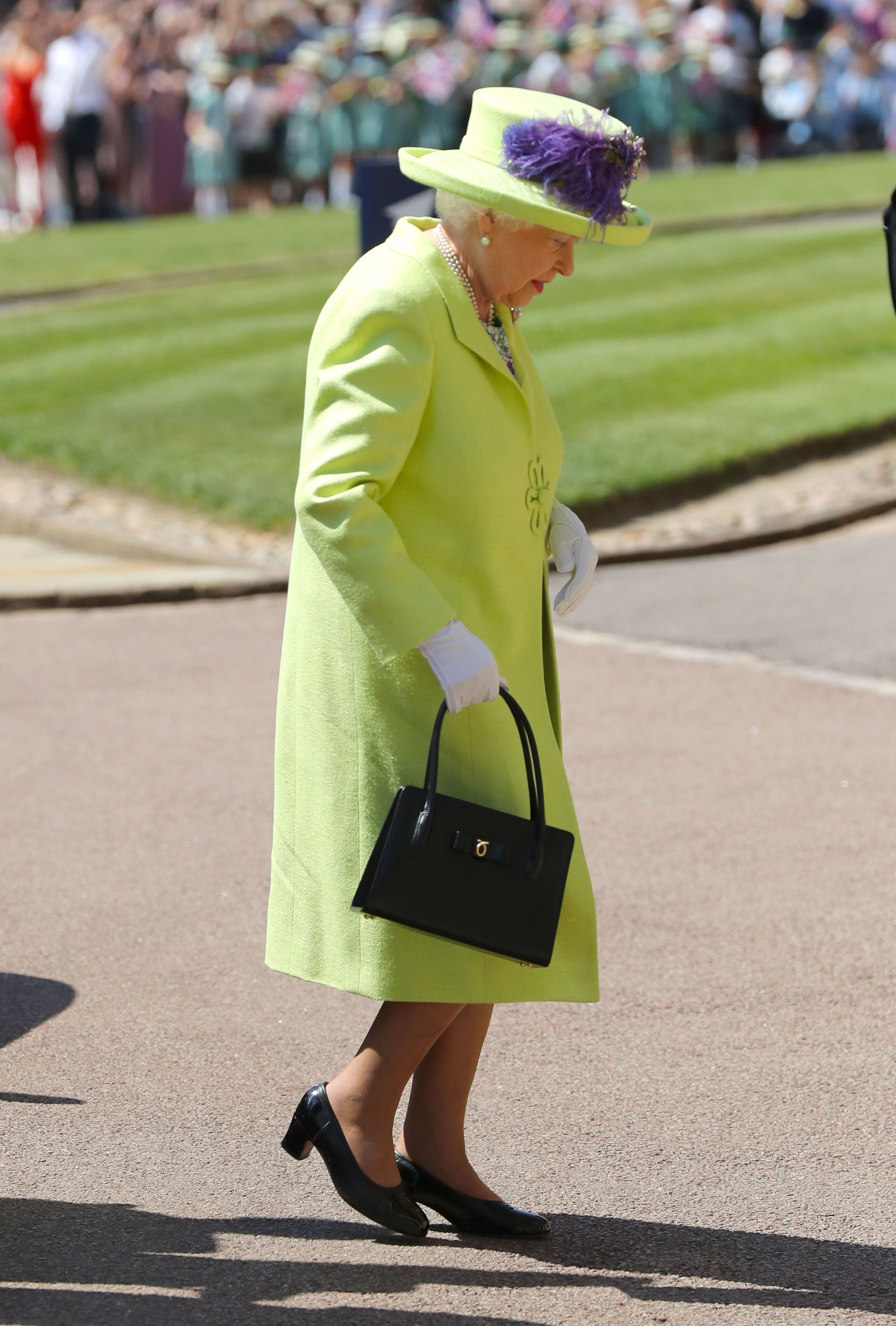 Her Majesty is wearing a flared dress in lime, lemon, purple and grey printed silk and a lime green tweed coat, both by Stuart Parvin.