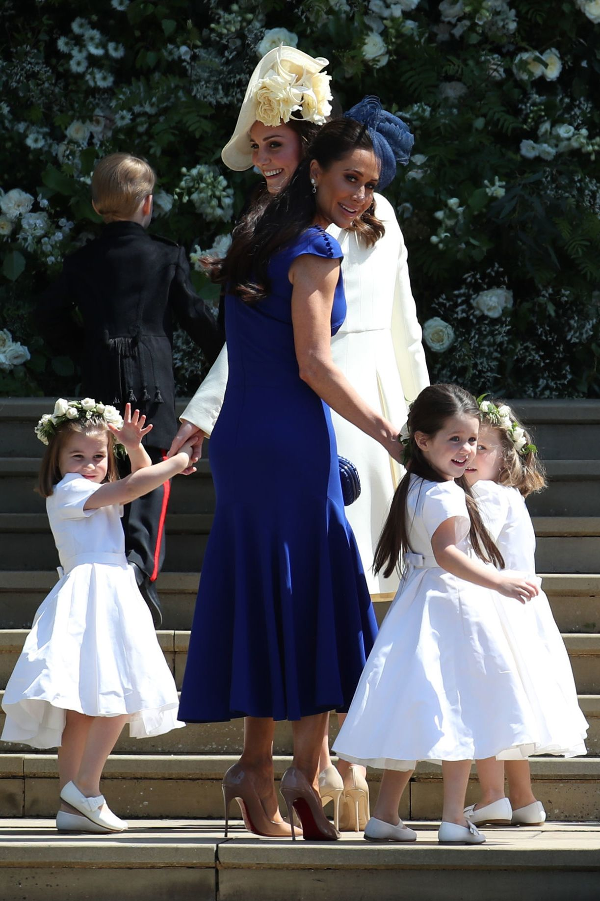 Meghan's best friend Jessica Mulroney wears a royal blue custom tea-length fit and flare dress with cap sleeve button detail by Montreal-based designer Di Carlo Couture with Christian Louboutin heels. MORE : Who Meghan Markle's Best Friend Jessica Mulroney?