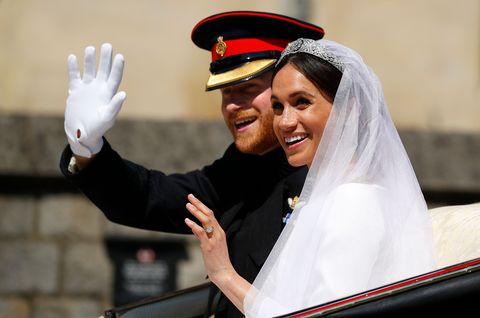 topshot   britains prince harry, duke of sussex and his wife meghan, duchess of sussex wave from the ascot landau carriage during their carriage procession on castle hill outside windsor castle in windsor, on may 19, 2018 after their wedding ceremony photo by phil noble  pool  afp        photo credit should read phil nobleafp via getty images