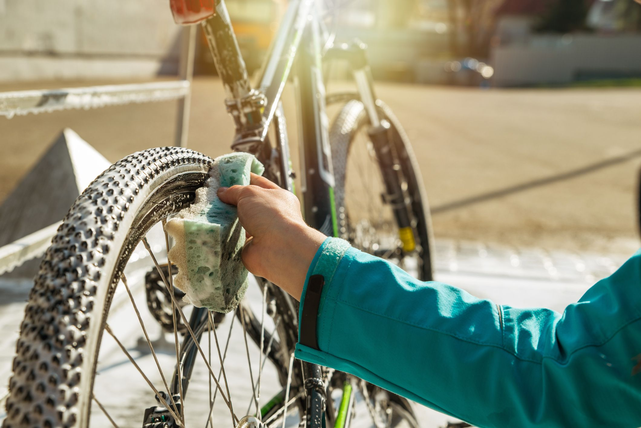 woman hand cleaning bicycle wheel with sponge.