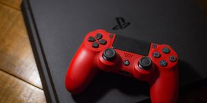 A Sony PlayStation 4 video game console with a red wireless