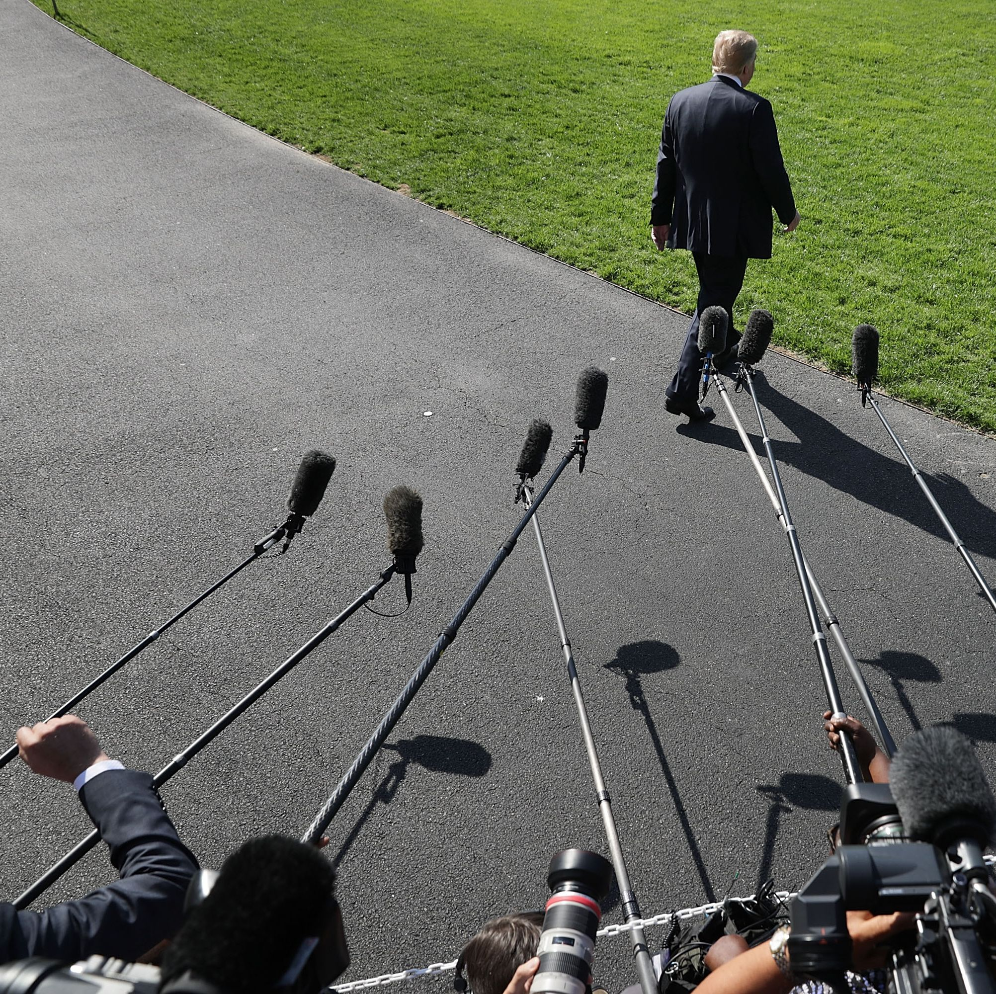 Trump walks toward the waiting Marine One after talking to members of the news media before departing the White House on May 25, 2018