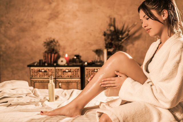 beautiful relaxed young woman in bathrobe putting lotion on her skin