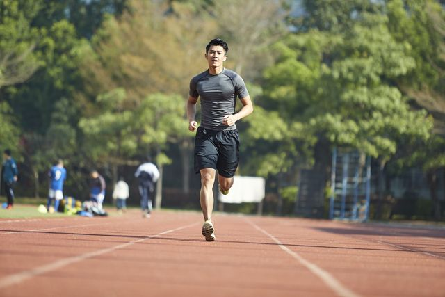 young asian man male athlete running training exercising on track, rear view