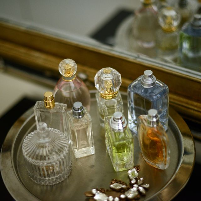 Perfume bottles on a tray by a mirror