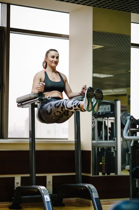 young fitness woman hanging and performing working with abdominal muscles press on the horizontal bar, raises his legs up in gym club fitness, sport, training concept