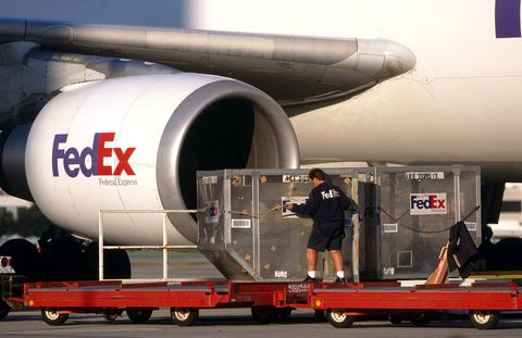 men moving LD3 containers on trolleys with CF6-80 engine-intake of a FedEx Airbus A300-600 freighter