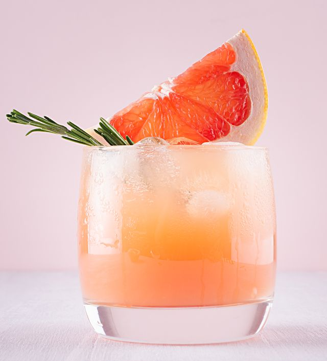 cold detox cocktail of grapefruit juice with ice, rosemary, slices citrus on soft light pink and white background